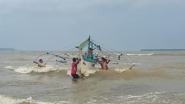 Des Philippins mettent en sécurité un bateau de pêche sur la côte à Borongan, dans le centre des Philippines, le 2 décembre 2019 à l'approche du typhon Kammuri [Alren BERONIO / AFP]
