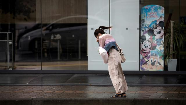 Une Japonaise lutte contre le vent lors du typhon Trami à Kagoshima (sud-ouest) le 30 septembre 2018. [Behrouz MEHRI / AFP]