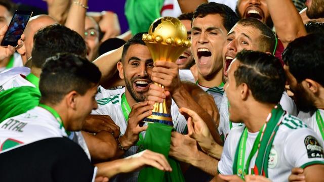 L'attaquant Riyad Mahrez (c) soulève le trophée après la victoire de l'équipe d'Algérie contre le Sénégal en finale de la CAN-2019, le 19 juillet 2019 au Caire [Giuseppe CACACE / AFP]