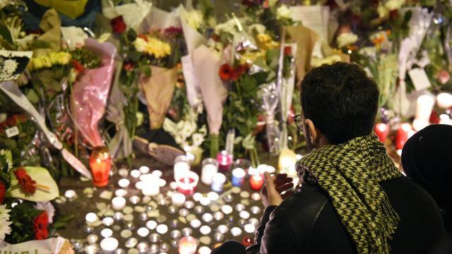 Un homme rend hommage aux victimes des attaques du Bataclan, le 14 novembre 2015 à Paris [FRANCK FIFE / AFP]