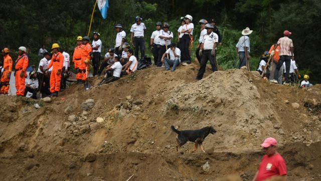 Des secouristes, pompiers et habitants sur les lieux d'un glissement de terrain à Santa Catarina Pinula, à 15 km à l'est de Guatemala, le 2 octobre 2015 [JOHAN ORDONEZ / AFP]