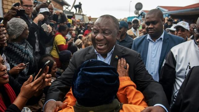 Le président sud-africain Cyril Ramaphosa salue des partisans en allant voter à Soweto, le 8 mai 2019. [Michele Spatari / AFP]