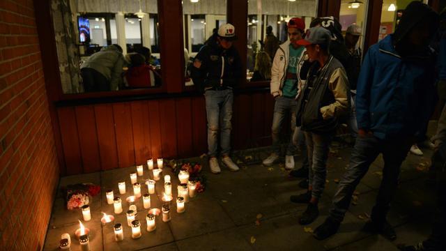 Des bougies sont allumées devant l'école de Trollhättan, en Suède, où un homme armé d'un sabre, réputé proche de l'extrême droite, a tué deux personnes [JONATHAN NACKSTRAND / AFP]