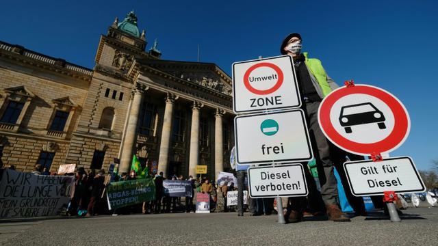 Des militants écologistes manifestent devant La Cour administrative fédérale de Leipzig qui doit rendre un verdict sur l'interdiction des vieux diesels dans les centres-villes les plus pollués, le 22 février 2018 en Allemagne [Sebastian Willnow / dpa/AFP/Archives]