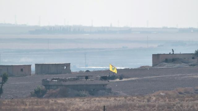 Photo prise depuis le côté turc de la frontière turco-syrienne, montrant un drapeau des Unités de protection du peuple (YPG) flottant au-dessus d'un bâtiment près de la ville syrienne de Tal Abyad, le 8 octobre 2019 [BULENT KILIC / AFP]