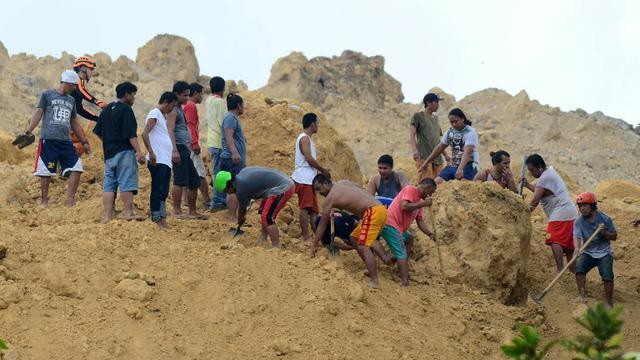 Des habitants et des sauveteurs à la recherche de survivants après un glissement de terrain déclenché par des pluies de mousson, le 20 septembre 2018 à Naga, sur l'île philippine de Cebu [ALAN TANGCAWAN / AFP]