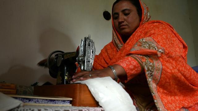 Hajra Bibi coud des serviettes hygiéniques, le 18 mai 2019 dans le village pakistanais de Booni [AAMIR QURESHI / AFP]