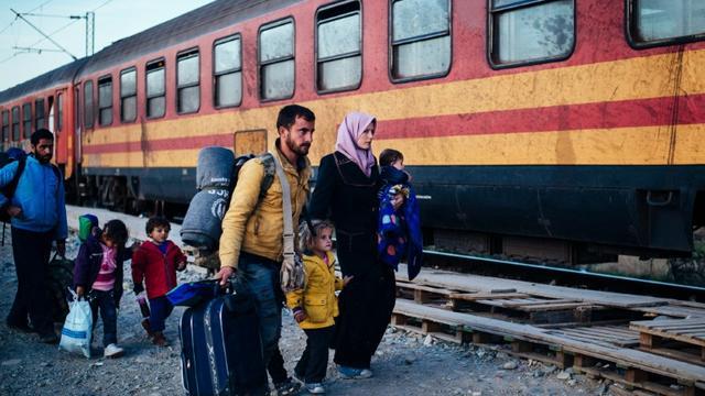 Une famille, parmi d'autres migrants, s'apprête à monter dans un train se dirigeant vers la Serbie après avoir passé la frontière gréco-macédonienne près de Gevgelija, en Macédoine, le 16 novembre 2015 [DIMITAR DILKOFF / AFP/Archives]