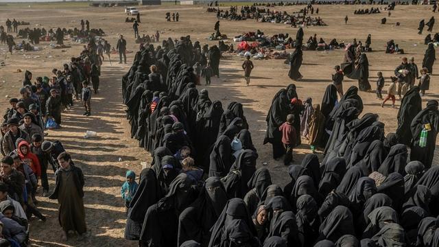 Des personnes attendent d'être fouillés par les Forces démocratiques  syriennes après avoir quitté le dernier réduit de Daesh, à Baghouz, dans l'est de la Syrie, le 5 mars 2019.