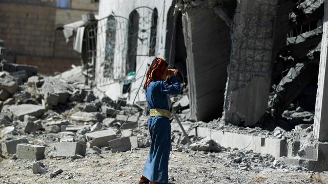 Un homme se tient devant un immeuble détruit par un bombardement de la coalition menée par l'Arabie saoudite, à Sanaa le 28 octobre 2015 [MOHAMMED HUWAIS / AFP/Archives]