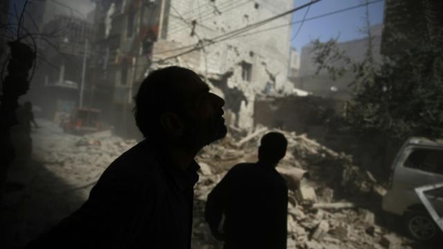Des Syriens regardent les dégâts provoqués par des frappes aériennes sur la zone rebelle de Douma, à l'est de Damas, le 2 octobre 2015 [ABD DOUMANY / AFP]