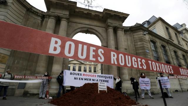Des activistes déversent de la boue rouge devant le ministère de l'Ecologie le 12 février 2019 à Paris [Thomas SAMSON / AFP]