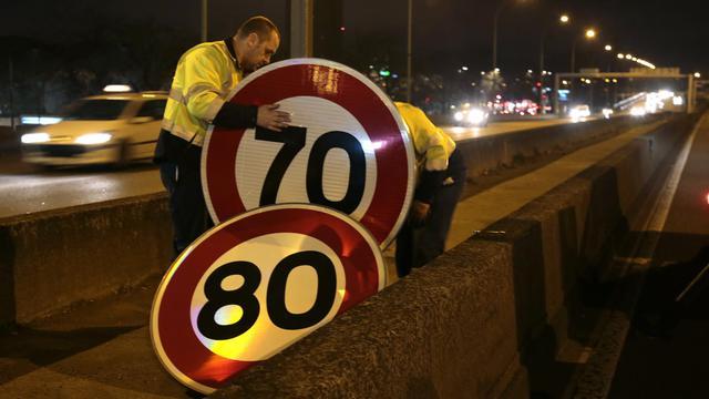 Des employés municipaux changent les paneaux de limitation de vitesse le 7 janvier 2014 sur le boulevard périphérique à Paris [Jacques Demarthon / AFP]