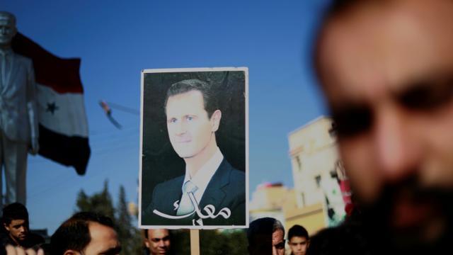 Des manifestants brandissent une photo du président syrien Bachar al-Assad à Qamichli, dans le nord du pays, le 23 décembre 2018 demandant la protection de l'armée [Delil SOULEIMAN / AFP]