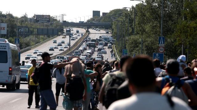 Des migrants partis de la gare de Budapest empruntent à pied une autoroute en direction de l'Autriche, le 4 septembre 2015 [Ferenc Isza / AFP]