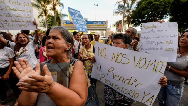 Des manifestants brandissent des pancartes demandant un référendum contre le président Nicolas Maduro, le 21 octobre 2016 à Caracas [Federico PARRA / AFP]