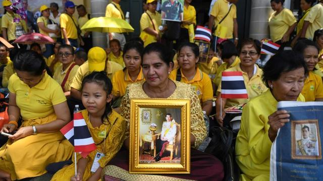 Des Thaïlandaises tiennent le portrait du roi Maha Vajiralongkorn, près du Grand palais, en attendant la grande parade pour son couronnement dans les rues de Bangkok, le 5 mai 2019 [Lillian SUWANRUMPHA / AFP]