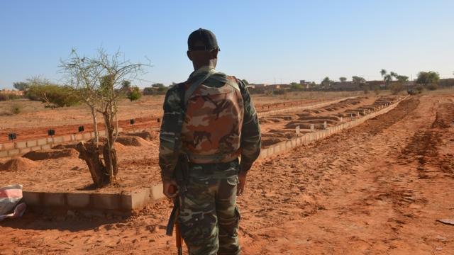 Un soldat nigérien devant les tombes de militaires tués, le 15 décembre 2019 à Niamey [Boureima HAMA / AFP/Archives]