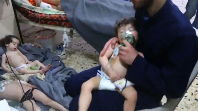 Une image prise sur une vidéo de la Défense civile syrienne montre des volontaires aidant des enfants victimes d'une attaque chimique présumée à Douma, le 8 avril 2018 [HO / AFP]