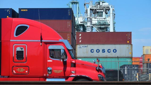Un camion passe devant des conteneurs, dont l'un appartenant au groupe chinois Cosco, le 6 juillet 2018 dans le port de Long Beach, en Californie [Frederic J. BROWN / AFP/Archives]