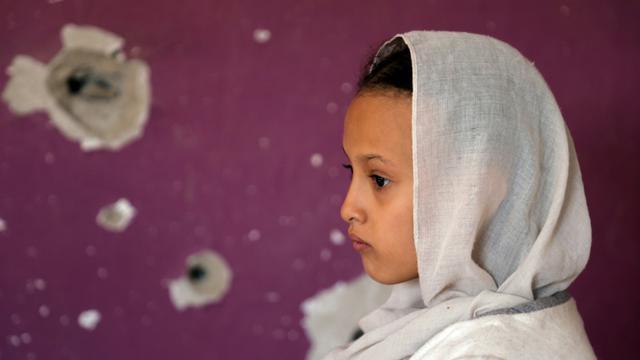 Une jeune fille yéménite, devant un mur criblée de balles, à Taez (Yémen), le 30 septembre 2018 [Ahmad AL-BASHA / AFP/Archives]