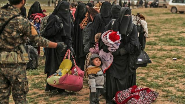 Un combattant des Forces démocratiques syriennes surveille des personnes évacuées du dernier réduit du groupe Etat islamique à Baghouz, dans l'est syrien, le 27 février 2019  [Delil SOULEIMAN / AFP]