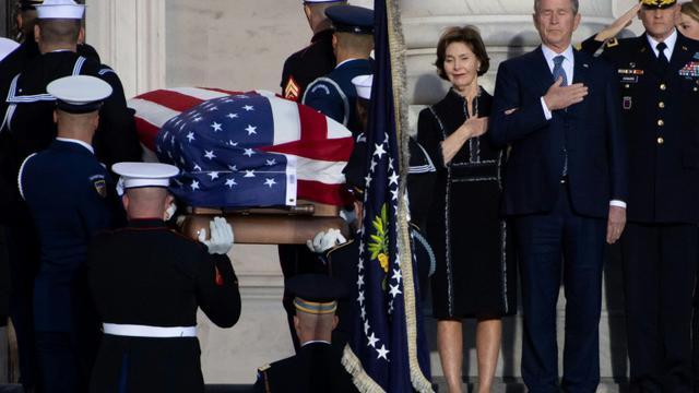 L'ancien président américain George W. Bush et son épouse Laura se recueille à l'arrivée du cercueil de George H. W. Bush au Capitole, le 3 décembre 2018 [SAUL LOEB / AFP]