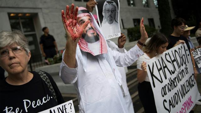 Un homme déguisé en Mohammed ben Salmane avec du sang sur ses mains manifeste devant l'ambassade saoudienne à Washington le 8 octobre 2018 contre la disparition du journaliste saoudien Jamal Khashoggi après être entré au consulat saoudien à Istanbul. [Jim WATSON / AFP]