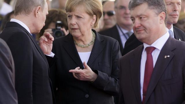 Le 6 juin 2014, la chancelière allemande Angela Merkel, invitée à la commémoration du 70e anniversaire du débarquement en Normandie (France), semblait jouer les go-between entre Vladimir Poutine (g) et Petro Porochenko (d), en marge des cérémonies  [Saul Loeb / AFP/Archives]