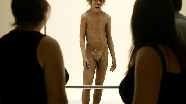 Des visiteurs observent la représentation d'un homme de Néandertal, le 19 juillet 2004 au musée national de la Préhistoire des Eyzies-de-Tayac, près de la grotte de Lascaux [PATRICK BERNARD / AFP/Archives]
