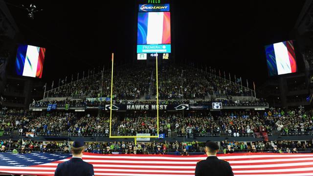 Des drapeaux français sont hissés, le 15 novembre 2015 dans un stade à Seattle en hommage aux victimes des attaques de Paris [Steve Dykes / GETTY IMAGES NORTH AMERICA/AFP]