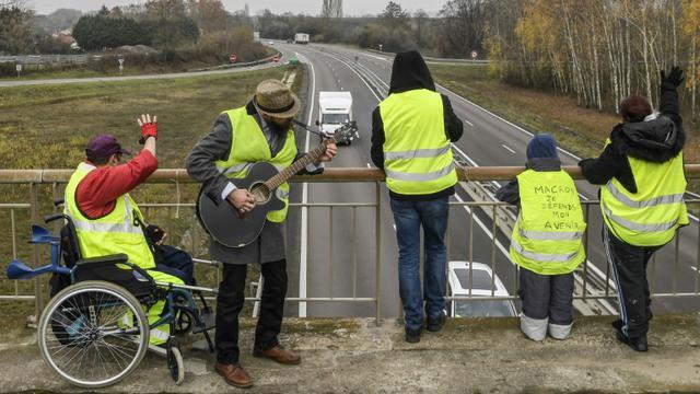 """Des """"gilets jaunes"""" manifestent le 21 novembre 2018 sur un pont au-dessus de la N70 près de Montceau-les-Mines [PHILIPPE DESMAZES / AFP]"""