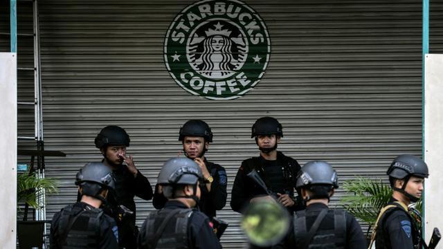 Des policiers indonésiens devant le café initialement visé par les terroristes à Jakarta, le 16 janvier 2016 [MANAN VATSYAYANA / AFP]