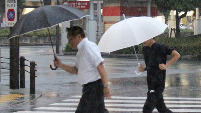 Des piétons sous la pluie à Tokushima au Japon, le 23 août 2018 [JIJI PRESS / JIJI PRESS/AFP]