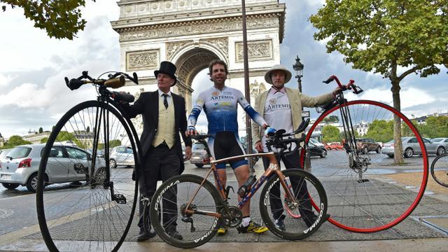 Le cycliste britannique Mark Beaumont (C) pose au côté de deux hommes et leur vélo grand-bi le 18 septembre 2017 à Paris [CHRISTOPHE ARCHAMBAULT / AFP]