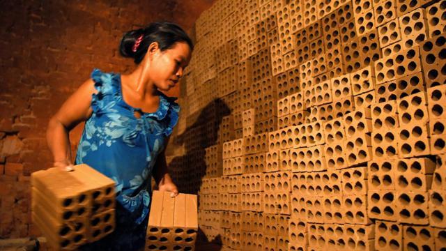 Une cambodgienne travaille dans une fabrique de briques dans la banlieue de Phnom Penh, le 11 décembre 2018 [TANG CHHIN Sothy / AFP]