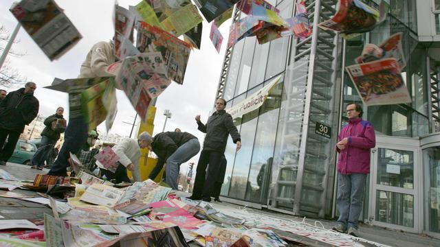 L'organisation Résistance à l'agression publicitaire (RAP) déverse des prospectus, le 09 décembre 2006 devant un centre commercial à Paris, lors d'une action de résistance à l'agression publicitaire pour protester contre les publicités distribuées dans les boîtes aux lettres [Jack Guez / AFP/Archives]