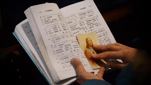 Photo du 12 février 2013 à la cathédrale de Shanghai montrant un missel et une image pieuse: la communauté catholique chinoise serait forte de 12 millions de fidèles dont la moitié sous contrôle officiel et l'autre loyale au Vatican   [Mark Ralston / AFP/Archives]
