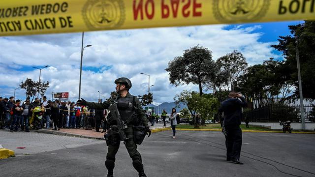 Policiers en faction sur le site de l'attentat qui a fait 20 morts à Bogota, le 17 janvier 2019 [Juan BARRETO / AFP]
