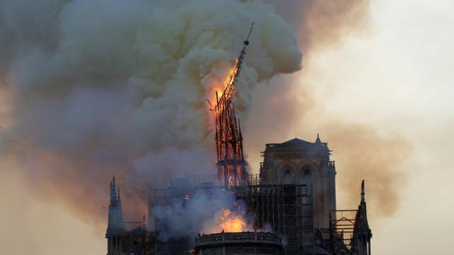 La flèche de Notre-Dame de Paris s'effondre pendant le spectaculaire incendie du 15 avril 2019 [Geoffroy VAN DER HASSELT / AFP/Archives]