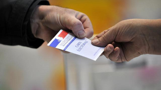 Un électeur présente sa carte électorale à un scrutateur [Thierry Zoccolan / AFP/Archives]