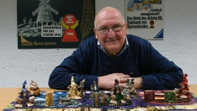 Tom Werneck, collectionneur de 79 ans, pose derrière un jeu de plateau aux archives Bayerisches Spielearchiv des jeux de société, à Munich, dans le sud de l'Allemagne, le 12 décembre 2018  [Christof STACHE / AFP]