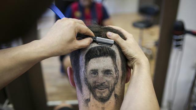 Le coiffeur serbe Mario Hvala dessine Messi sur l'arrière du crâne d'un client à Novi Sad, en Serbie, le 10 juin 2018  [VLADIMIR ZIVOJINOVIC / AFP]