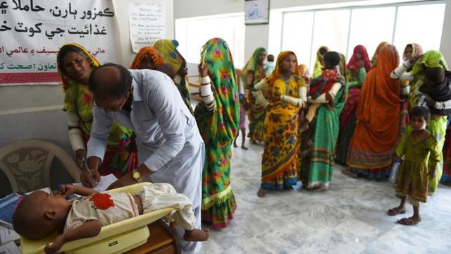 Un médecin vérifie le poids d'un enfant à l'hôpital pakistanais de Mithi, le 25 mai 2018 [RIZWAN TABASSUM / AFP]