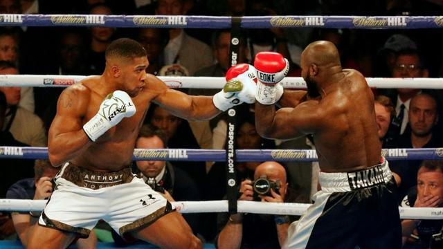 Le Britannique Anthony Joshua (g) face au Franco-Camerounais Carlos Takam pour défendre ses ceintures mondiales IBF et WBA des lourds, le 28 octobre 2018 à Cardiff [ADRIAN DENNIS / AFP]