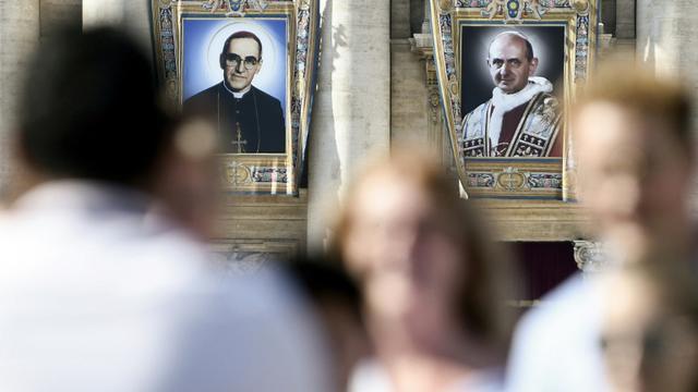 Portraits de l'archevêque salvadorien Oscar Romero (g) et du pape Paul VI (d) sur la façade de la Basilique Saint-Pierre, au Vatican, le 13 octobre 2018 [Filippo MONTEFORTE / AFP]