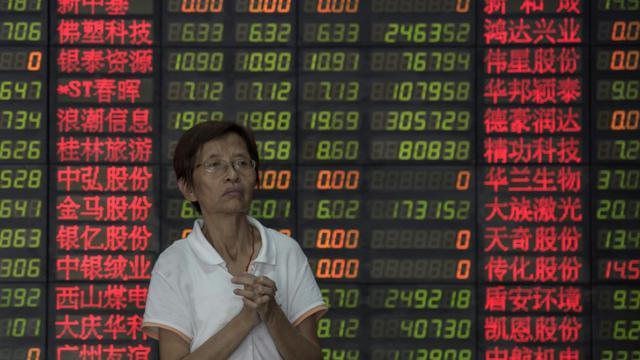 Un investisseur près d'un tableau électronique de cotations dans une société de Bourse de Shanghai le 1er septembre 2015 [JOHANNES EISELE / AFP]