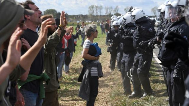 Des militants écologistes font face aux policiers dans la forêt de Hambach à Kerpen, en Allemagne le 15 septembre 2018. [Henning Kaiser / dpa/AFP]