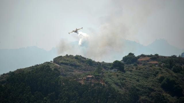 Un Canadair survole une forêt touchée par un incendie sur l'île espagnole de Grande Canarie, le 19 août 2019.  [DESIREE MARTIN / AFP]