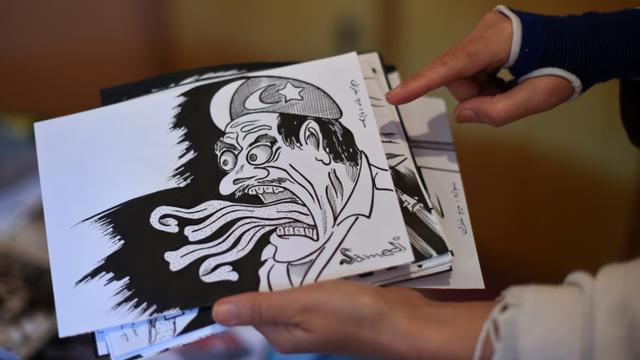 La satiriste afghane Masouda Khazan Tokhi montre une des caricatures sur laquelle elle travaille chez elle, à Kaboul, le 14 septembre 2015 [WAKIL KOHSAR / AFP]